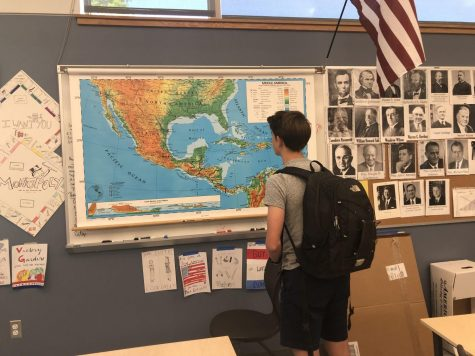 A junior examines a map in a Greylock history classroom.